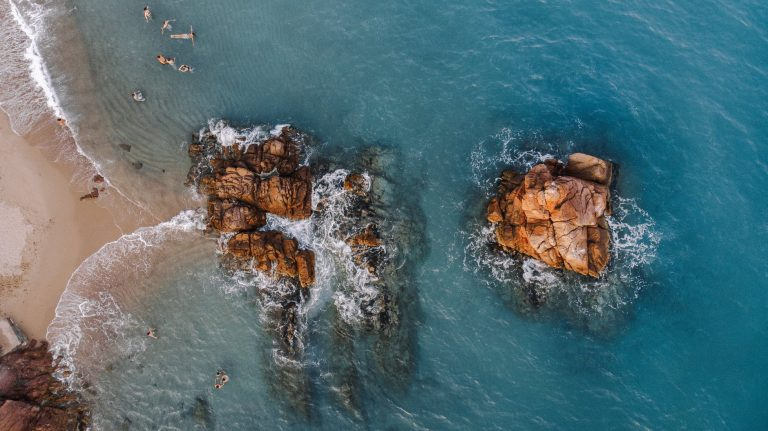 tourists swimming in ocean with cliffs