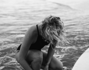 young woman in swimsuit with surfboard in sea